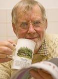 Ältere trinkende Tee- und lesenzeitung. Stockfotografie