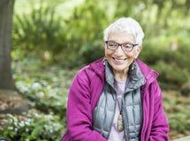 Ältere unabhängige Frau, die im Park glücklich u. im Lächeln sitzt Stockfotos