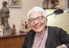 Ältere unabhängige Frau, die im Park glücklich u. im Lächeln sitzt Stockbild