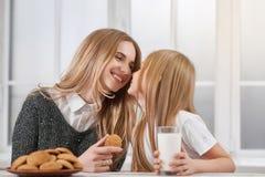 Ältere und jüngere Schwestern, die Plätzchen essen Stockfotografie