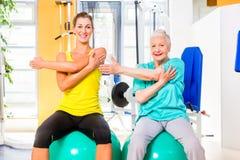 Ältere und junge Frau, die in der Eignungsturnhalle ausarbeitet Lizenzfreie Stockfotos
