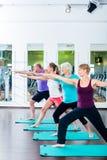 Ältere und junge Leute, die Gymnastik in der Turnhalle tun Stockbilder