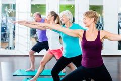 Ältere und junge Leute, die Gymnastik in der Turnhalle tun stockfotos