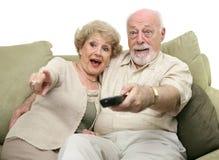 Ältere unterhalten durch Fernsehapparat lizenzfreie stockbilder