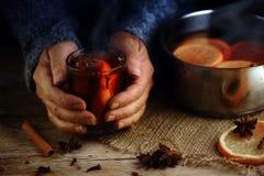 Ältere weibliche Hände, die als Nächstes einen Glasbecher mit heißem Glühwein halten lizenzfreie stockfotografie