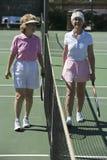 Ältere weibliche Tennis-Spieler, die am Netz stehen stockfotos