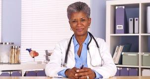 Älterer afrikanischer Doktor, der am Schreibtisch lächelt an der Kamera sitzt Stockfotografie