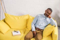 älterer Afroamerikanermann, der auf Couchbuch und -brillen schläft stockbild