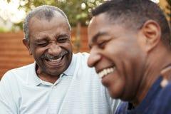 Älterer Afroamerikanermann und sein erwachsener Sohn, die zusammen draußen, Abschluss oben lacht stockfotos