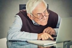 Älterer alter Mann, der die Laptop-Computer bei Tisch sitzt verwendet Stockfotografie