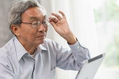 älterer alter Mann der Gläser glücklich unter Verwendung des Betrachtens des Tabletschirmes lizenzfreies stockbild