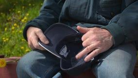 Älterer alter Mann im Ruhestand, der Kappe entfernend sitzt und sie in der Handnahaufnahme halten stock video