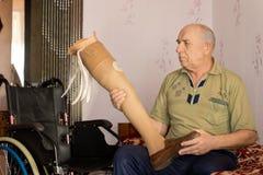 Älterer Amputierter, der ein künstliches Bein halten sitzt Stockbilder