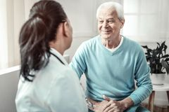 Älterer angenehmer Mann, der den Doktor sitzt und betrachtet lizenzfreie stockfotos