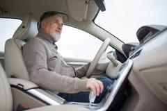 Älterer Antrieb, der sein modernes Auto, gehend in umgekehrtes fährt stockbilder