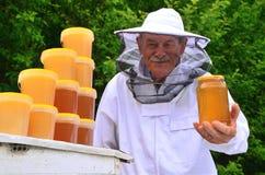 Älterer Apiarist, der Glas frischen Honig im Bienenhaus darstellt Stockfotos