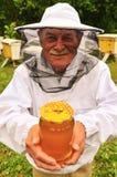 Älterer Apiarist, der Glas frischen Honig im Bienenhaus darstellt Lizenzfreies Stockfoto