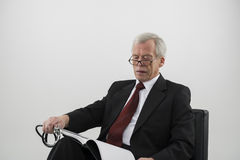 Älterer Arzt, der eine medizinische Zeitschrift liest Stockbild