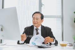 Älterer asiatischer finanziellgeschäftsmann, der herein an seinem Arbeitsplatz sitzt stockfotos