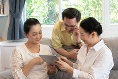 Älterer asiatischer Freund, der zusammen auf Sofa unter Verwendung der digitalen Tablette sitzt stockfotografie