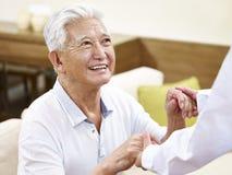 Älterer asiatischer Mann, der geholfen erhält Stockbild