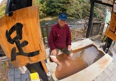 Älterer asiatischer Mann, der seine Füße an einer Thermalquelle tränkt Stockfoto
