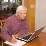 Älterer auf Laptop Stockfoto