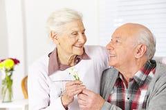Älterer Bürger, der Blume gibt