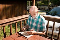 Älterer Bürger, der Sudoku spielt Lizenzfreie Stockfotos
