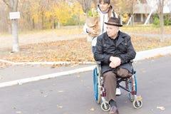 Älterer behinderter Mann, der bei seinem Einkaufen geholfen wird Stockfotos
