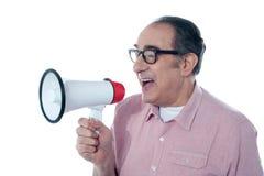Älterer beiläufiger Mann, der durch Megaphon schreit lizenzfreie stockfotos