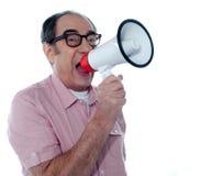 Älterer beiläufiger Mann mit Megaphon stockfotografie