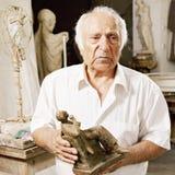 Älterer Bildhauer, der seine Skulptur anhält stockbild