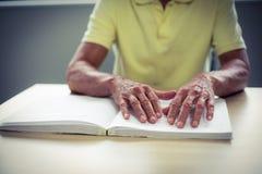 Älterer Blinder, der ein Blindenschrift-Buch liest Lizenzfreie Stockbilder