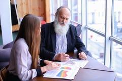 Älterer Chefmann unterzeichnet Dokument mit jungem Assistenten mit Papieren Stockbilder