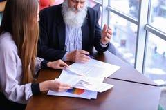 Älterer Chefmann unterzeichnet Dokument mit jungem Assistenten mit Papieren Stockbild