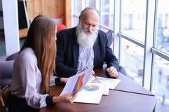 Älterer Chefmann unterzeichnet Dokument mit jungem Assistenten mit Papieren Stockfotografie
