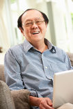 Älterer chinesischer Mann, der Laptop verwendet, während entspannend Stockfotos