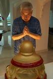 Älterer chinesischer Mann, der zur Statue von Buddha betet Lizenzfreies Stockfoto