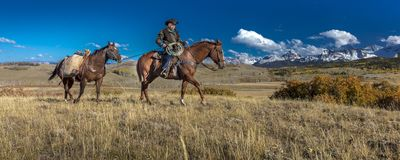 Älterer Cowboy führt Packpferd über historischer letzter Dollar-Ranch O Stockbilder
