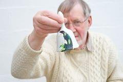 Älterer, der eine Glocke schellt, um Aufmerksamkeit zu verdienen. Stockfotografie