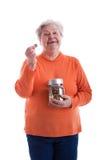 Älterer, der eine Münze und einen Sparungskasten anhält Lizenzfreie Stockfotos
