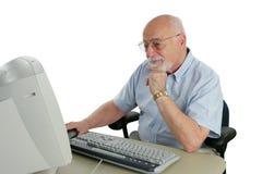 Älterer, der online erforscht Stockfotos
