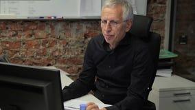 Älterer Direktor bearbeitet mit Computer in führender Firma bei Tisch sitzen stock video