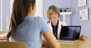 Älterer Doktor, der über Röntgenstrahl zum hispanischen Frauenpatienten spricht stockbild