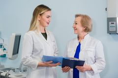 Älterer Doktor, der mit dem Assistenten der jungen Frau steht im gynäkologischen Büro mit Stuhl und in der Lampe auf spricht lizenzfreies stockbild