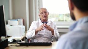 Älterer Doktor, der mit männlichem Patienten am Krankenhaus spricht stock footage