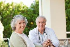 Älterer Doktor, der mit seinem fälligen Patienten spricht Stockfotos