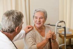 Älterer Doktor, der mit seinem Patienten spricht stockbilder