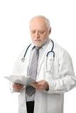 Älterer Doktor, der Papiere betrachtet Lizenzfreie Stockfotos